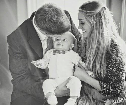 صورة ام و اب يلاعبان ابنهم الصغير